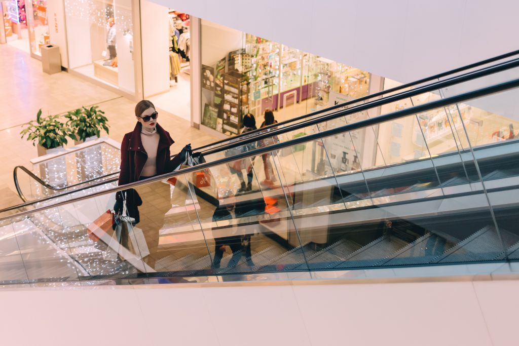 woman shopping at a mall going up an escalator with shopping bags